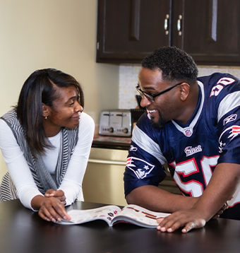 An African American couple takes a break from reading a magazine to gaze into each others eyes and smile.