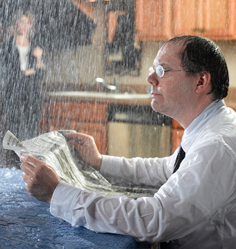 A man sits in his house reading the paper while he is doused by a leaky roof.